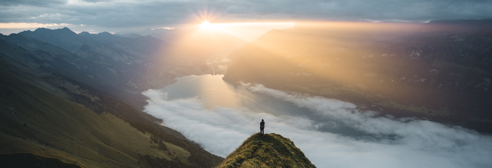 person on a hill at sunset