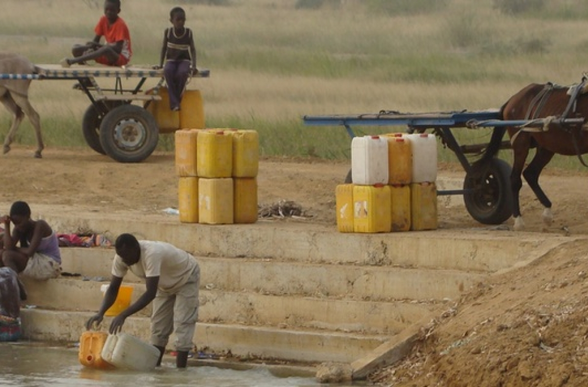 A man collects water from a river in Senegal.