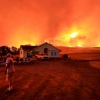Man looks back at his house while wildfire burns in the distance