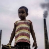 boy in front of smoke stacks