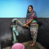 A woman pumps water from a shared community tap