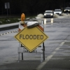 "a yellow diamond shaped sign reads ""FLOODED"" on a wet street"