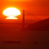 a large orange sun sets behind the Golden Gate Bridge