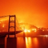 A fire burns on a hill behind a bridge with a bright orange sky