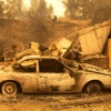 A burned car and house remains after a wildfire
