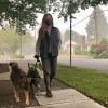 Woman walks with 2 dogs wearing a face mask down a smoky street