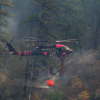 helicopter dropping water on a wildfire
