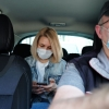 A woman sits in the backseat of a Lyft. She and the driver both wear face masks.