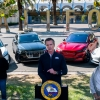 California gov. Gavin Newsom makes an announcement at a podium in front of electric vehicles