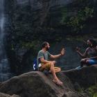 man and woman talking and sitting on a rock near a waterfall
