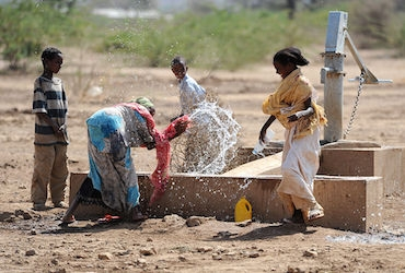 children playing by water pump