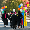 Students in caps and gowns with balloons