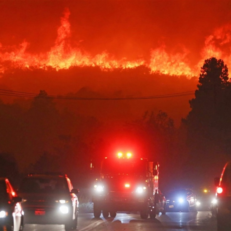cars on a road at night with a wildfire burning in the hills behind them