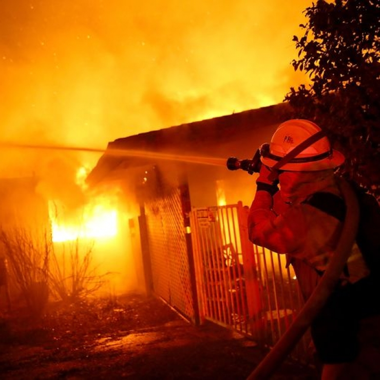 firefighter puts out wildfire burning a house