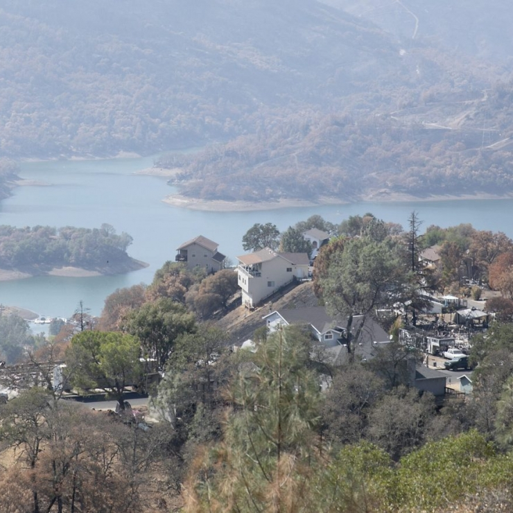 Photo of some homes burnt and some homes still standing above a lake