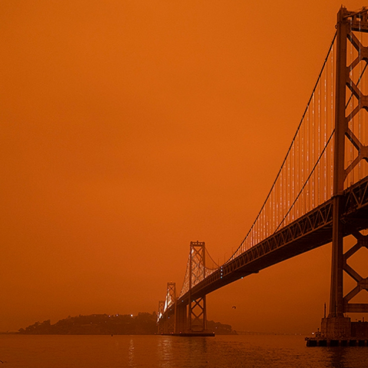 The golden gate bridge against a burnt orange sky