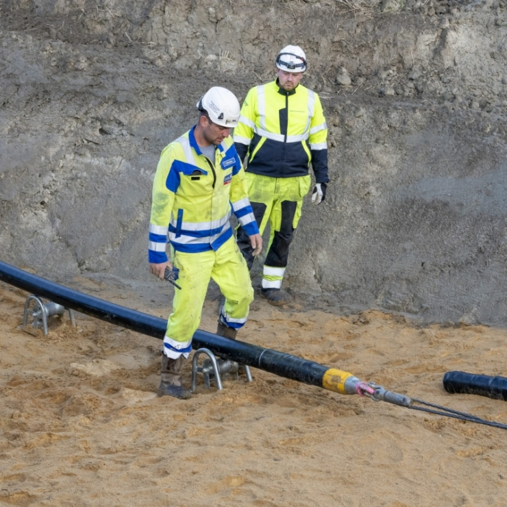 two men work on construction of a high voltage cable connecting Germany and Norway's electricity grids