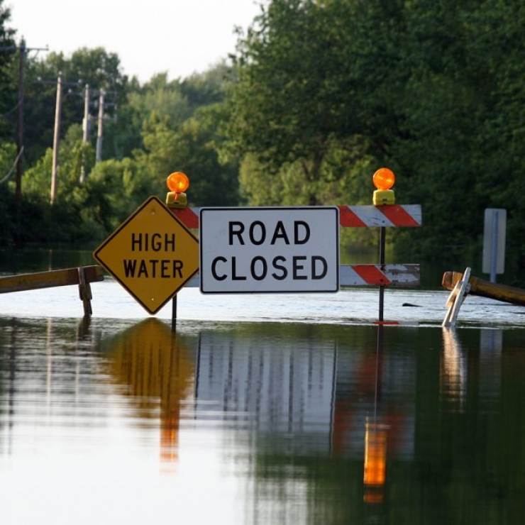 A flooded street with High Water and Road Closed caution signs