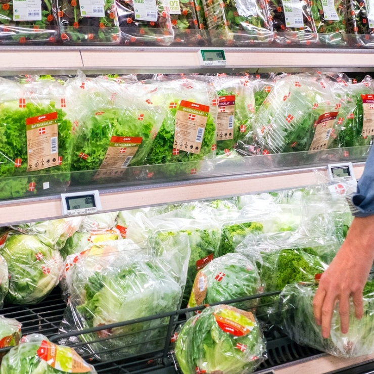 a hand reaches for packaged lettuce on grocery store refrigerated shelves