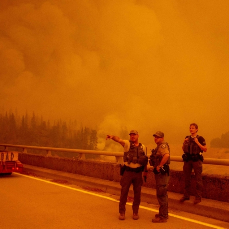 Officers stand on a bridge with an orange sky and wildfire smoke behind them
