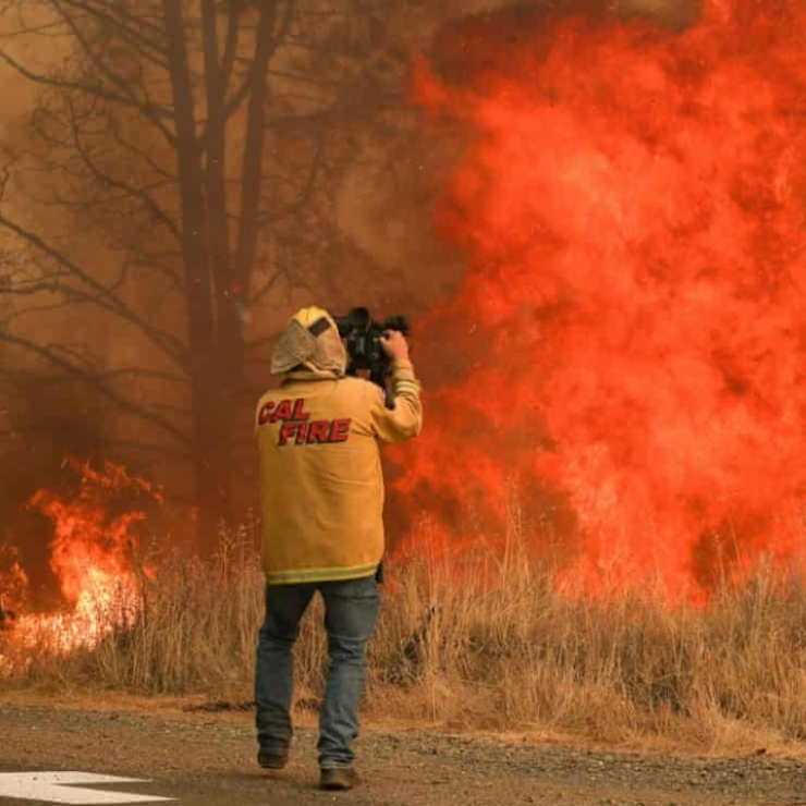A cameraman record a wildfire in California
