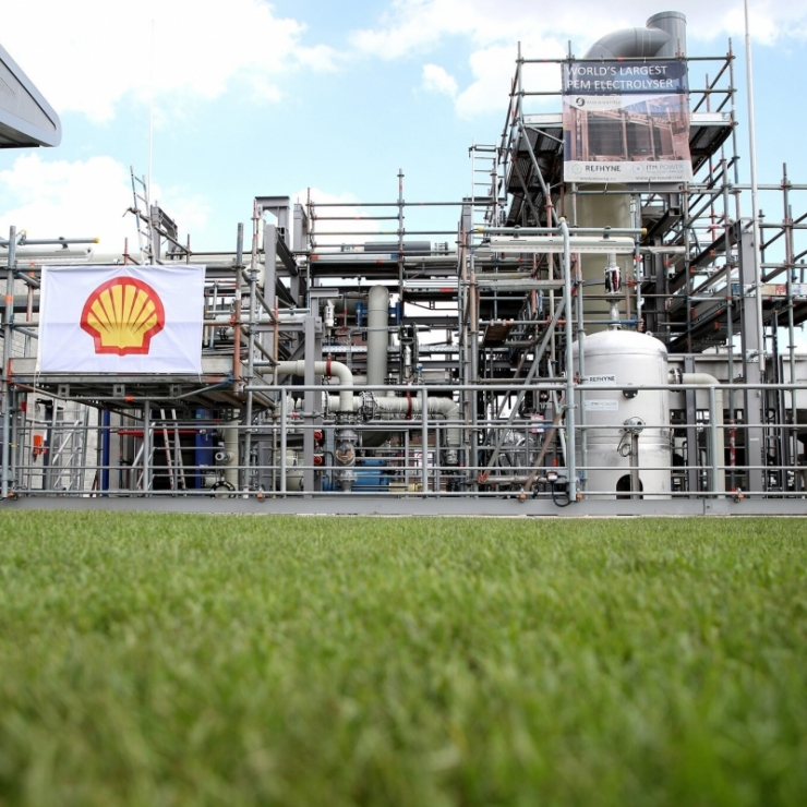 A German hydrogen production plant across a swath of green grass displays a Shell logo