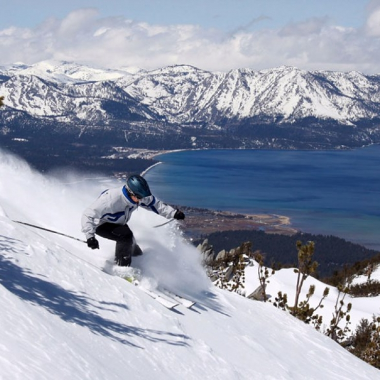 a person skiing down a hill with a snowy lake in the background