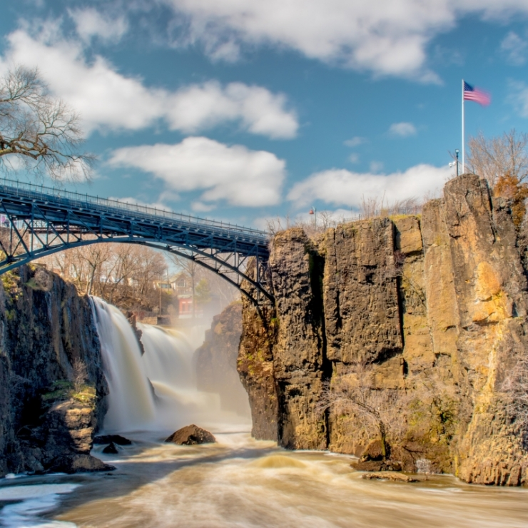 A waterfall behind a bridge in Great Falls Park, Paterson, United States