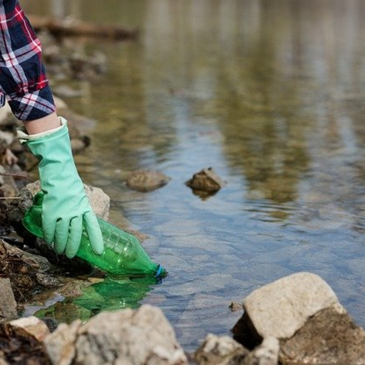 Person removing plastic waste from stream.
