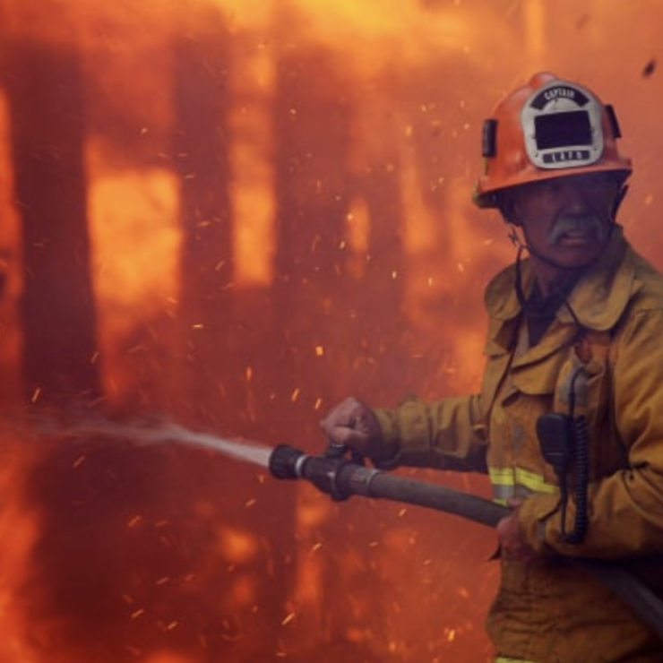 A firefighter sprays a water hose into wildfire flames.