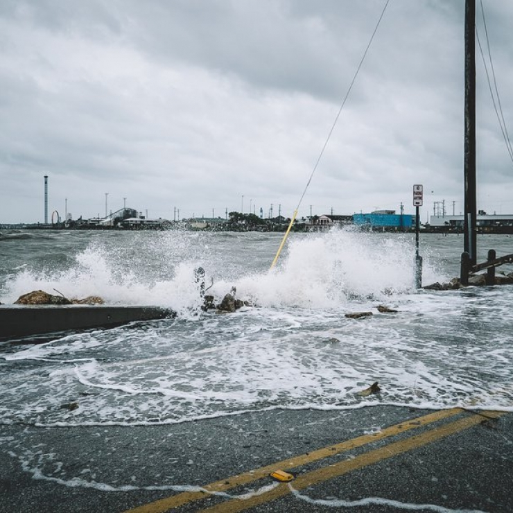 A wave from the ocean crashed against a broken wall flooding a street