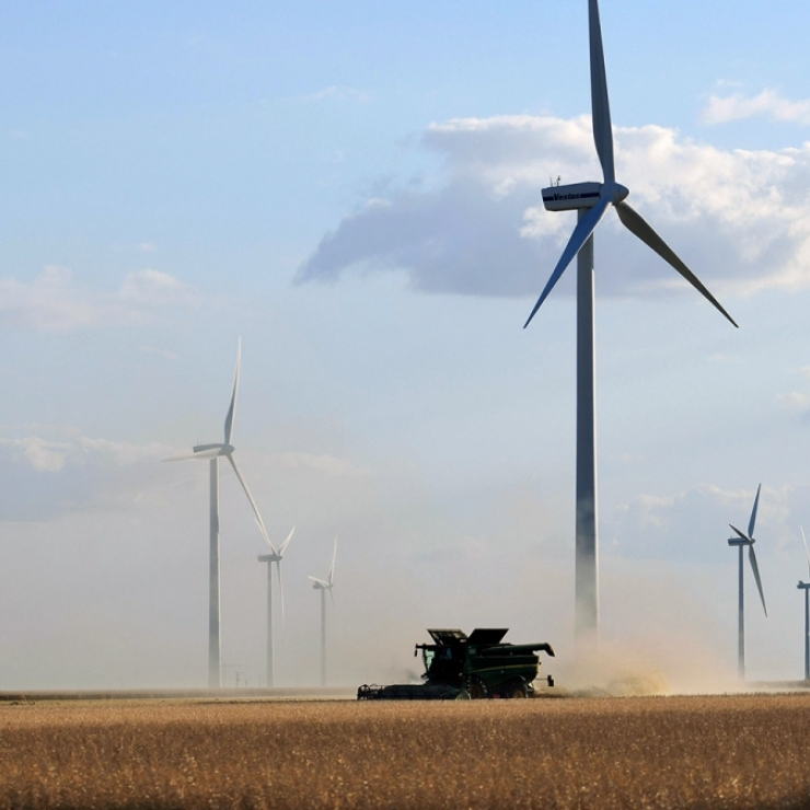 A tractor moves across a field and creates a cloud of dust as wind turbines spin in the background.